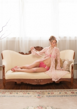 Woman in pink lace jacket lingerie by Accentuate Clothing on chaise lounge in boudoir