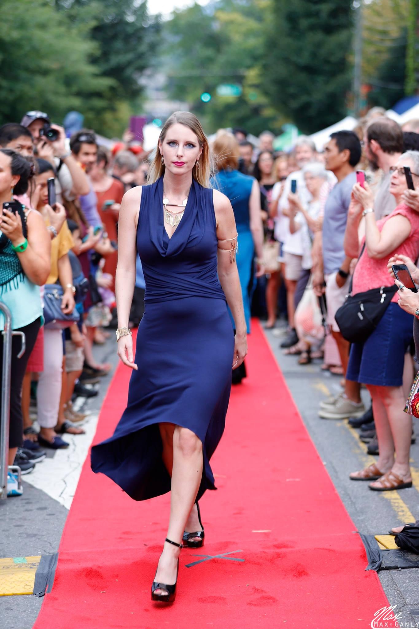 blonde woman walking down red carpet runway model